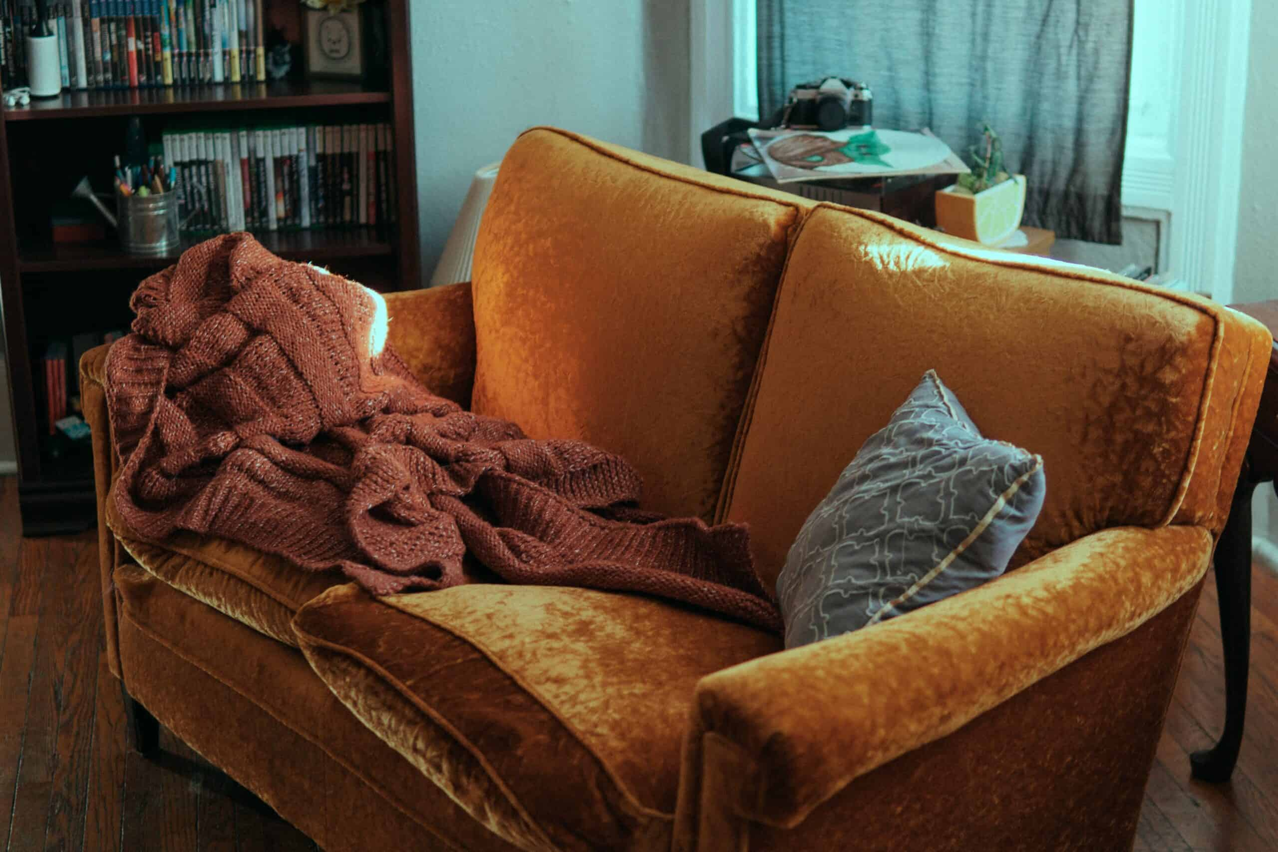 Couchsitting, blanket and cushion on a brown couch