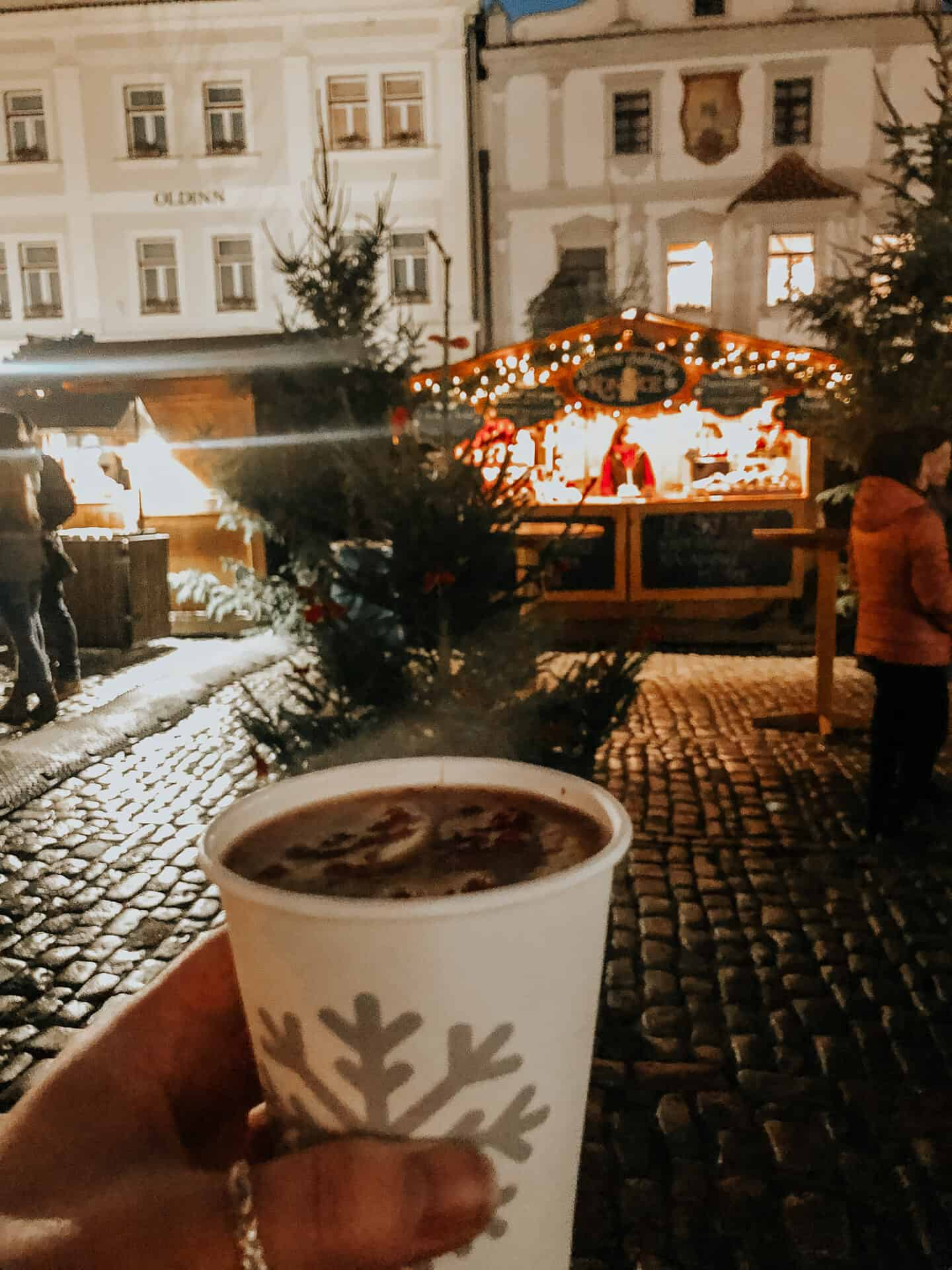 person holding a cup of mulled wine at a christmas market