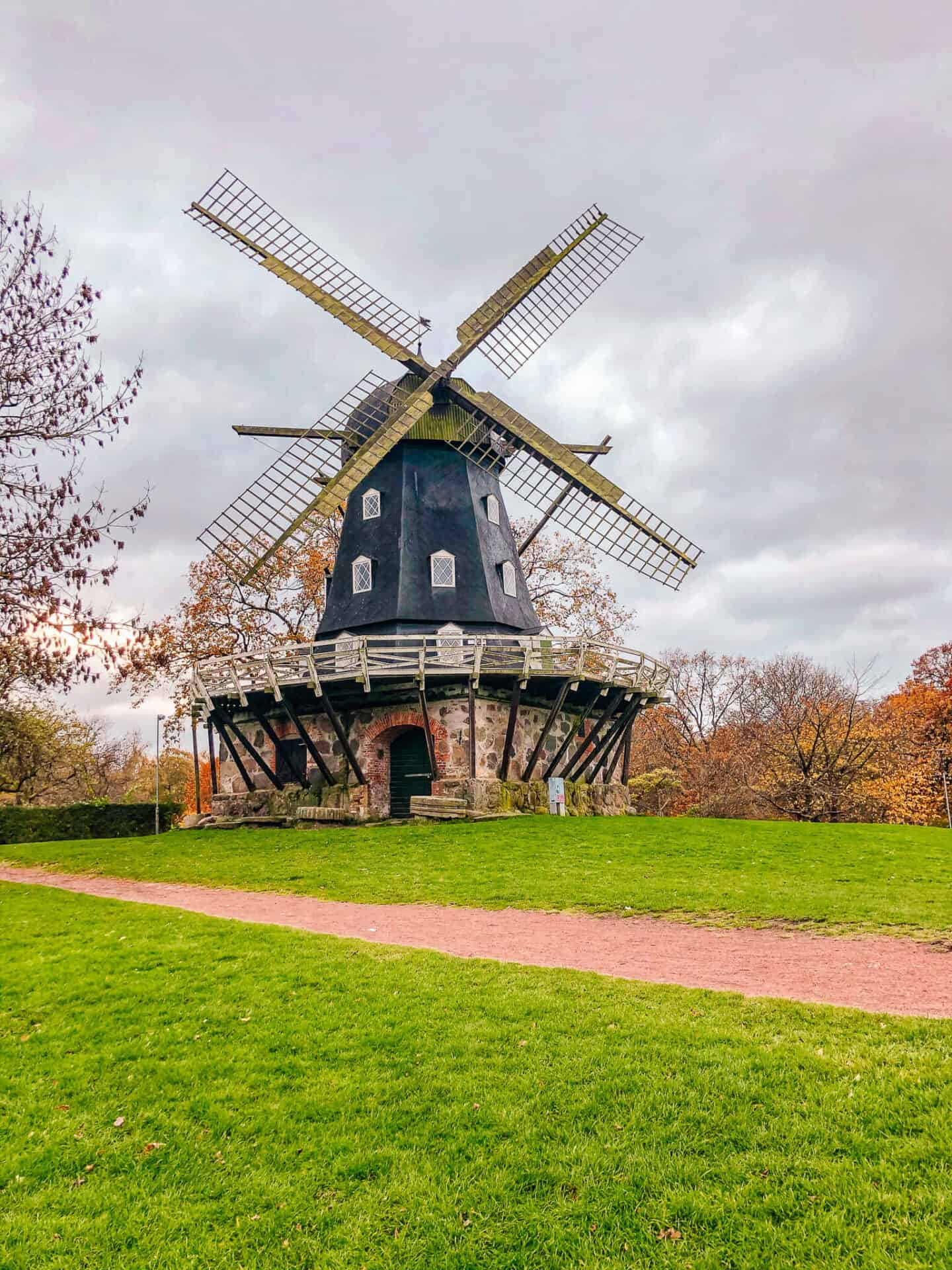 Blue windmill in the middle of bright green grass