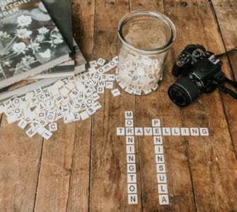 Scrabble pieces spelling Mornington Peninsula, camera and coffee table books