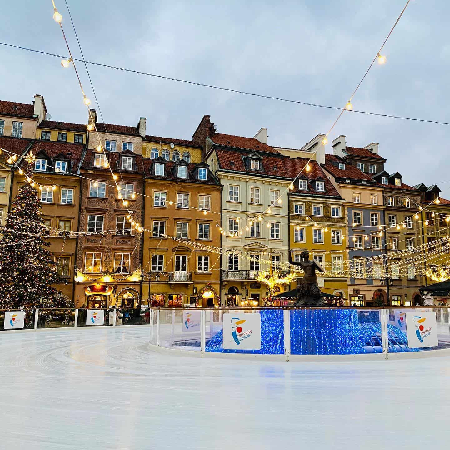 Ice skating rink surrounded by old buildings with fairy lights hanging over the ice skating rink