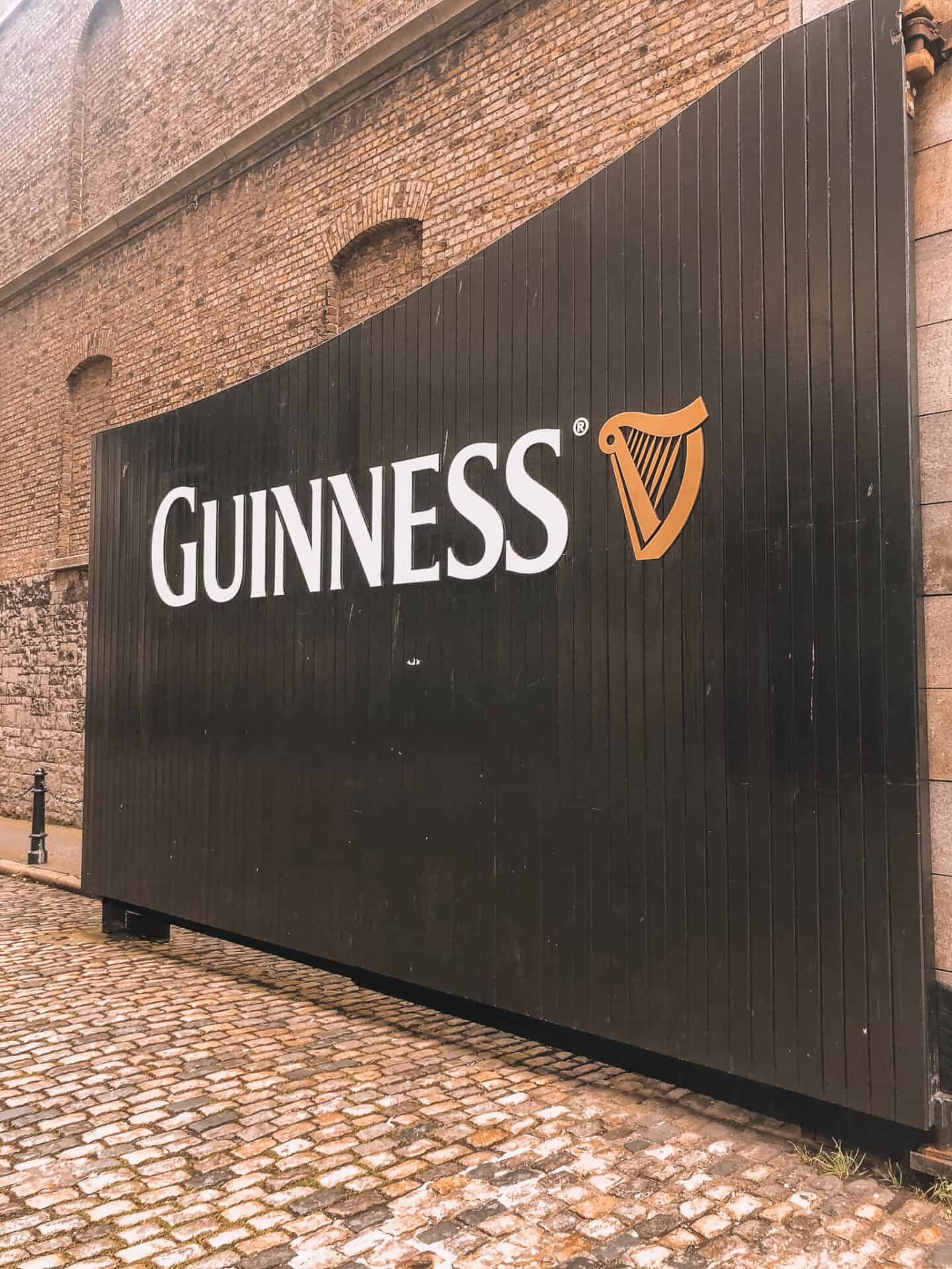 "A black gate with ""Guinness"" write on the gate."
