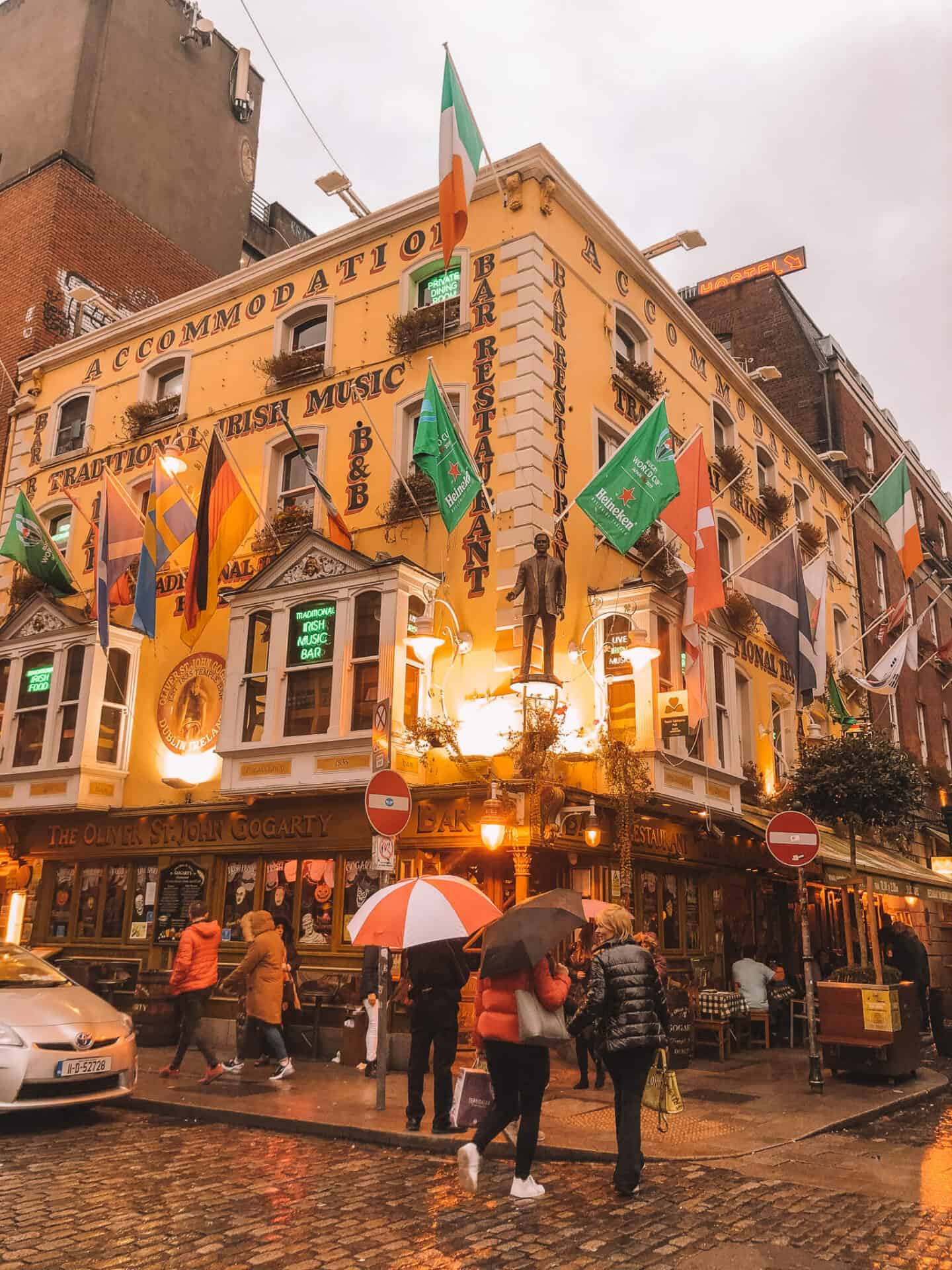 Decorate pub with people and umbrellas out the front