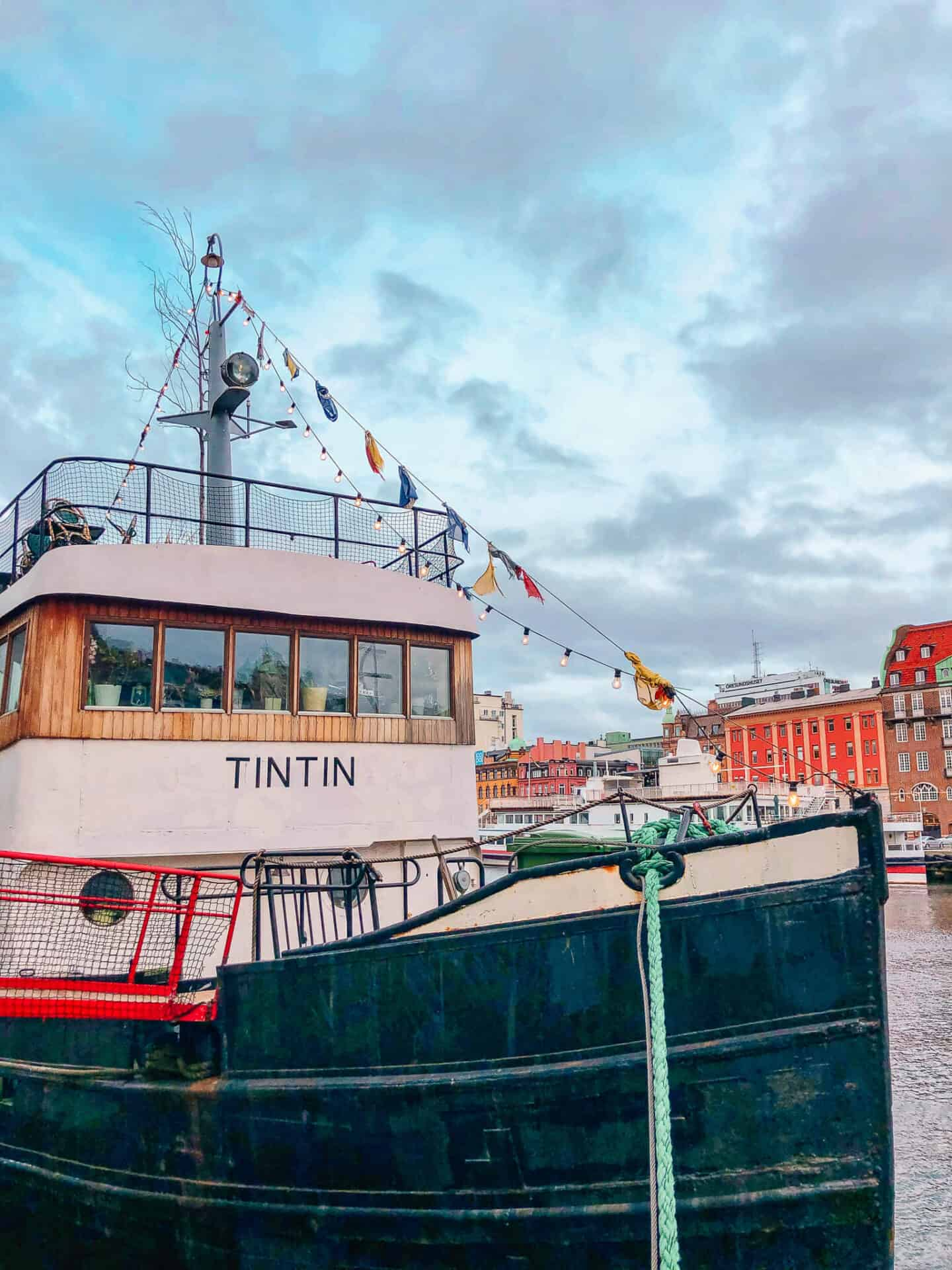 A green white and cream boat, titled Tin Tin