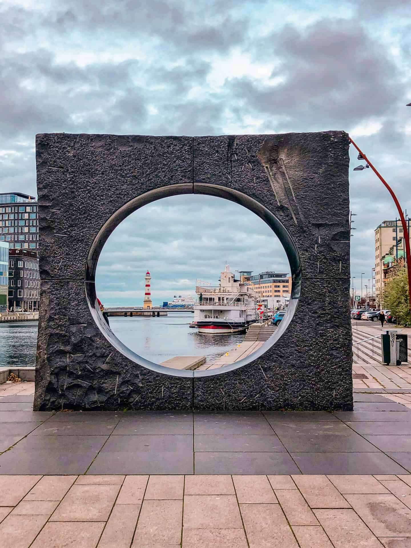 Stone square with a circle cut out and a harbour in the background