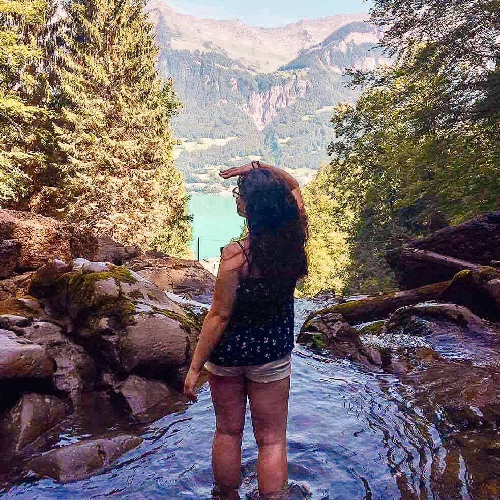 Girl standing in water looking over a waterful