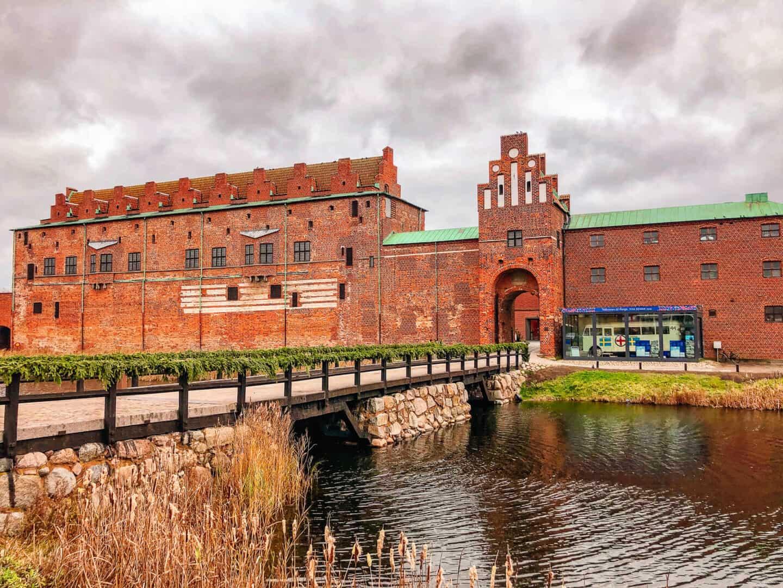 A brick castle with a bridge crossing over a river