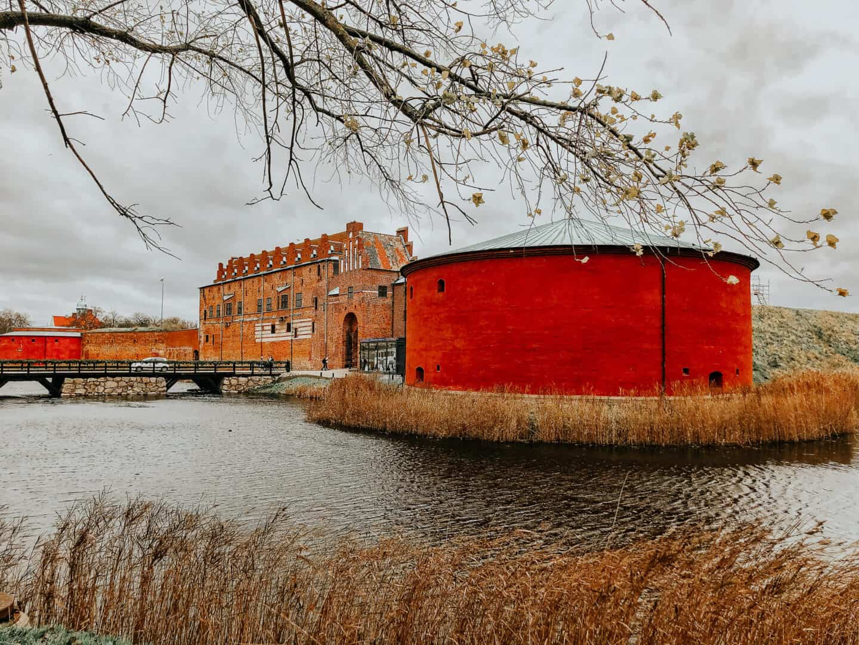 Red circular building next a brick building across the rive