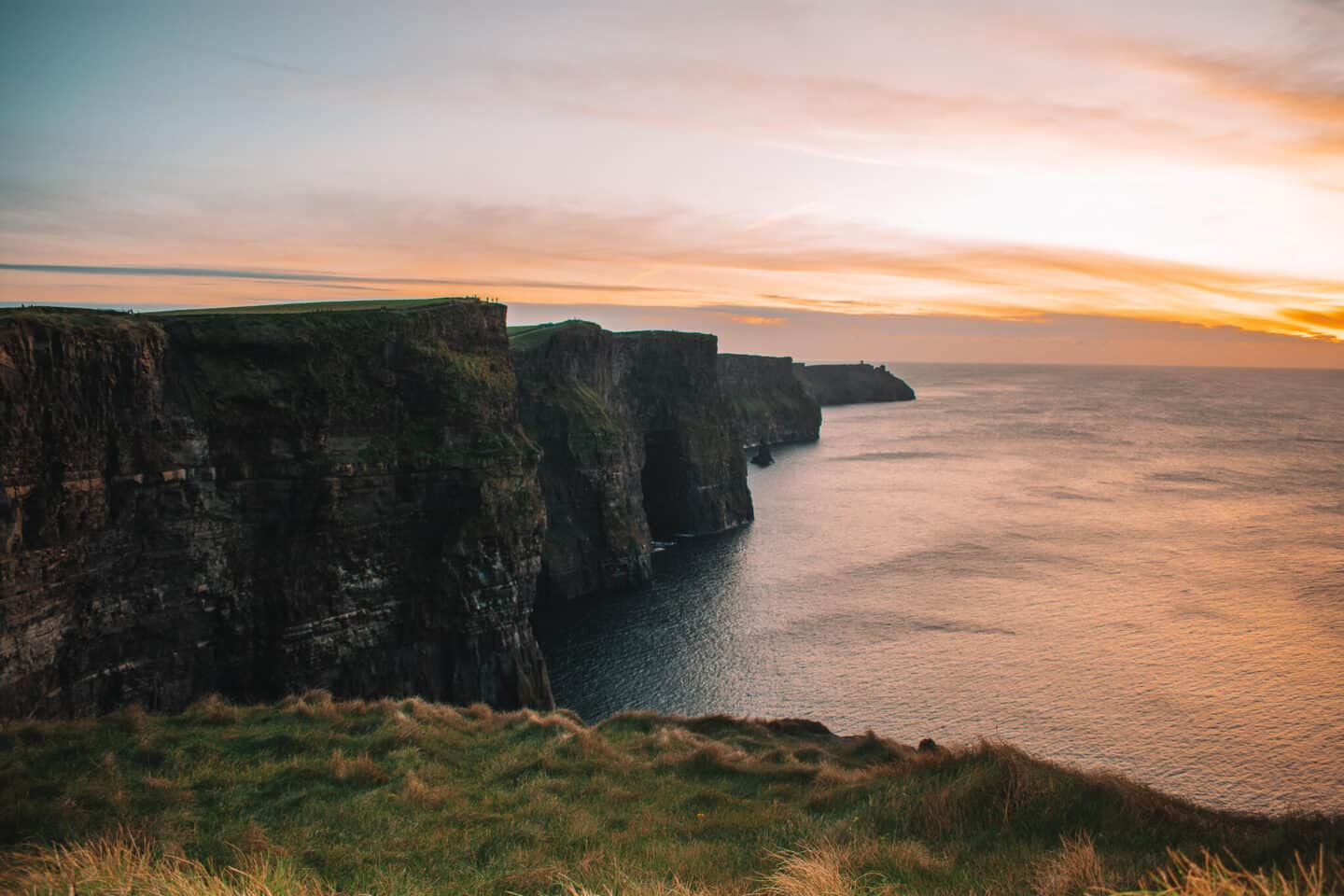 Rugged Cliffs rising out of the ocean at sunset.