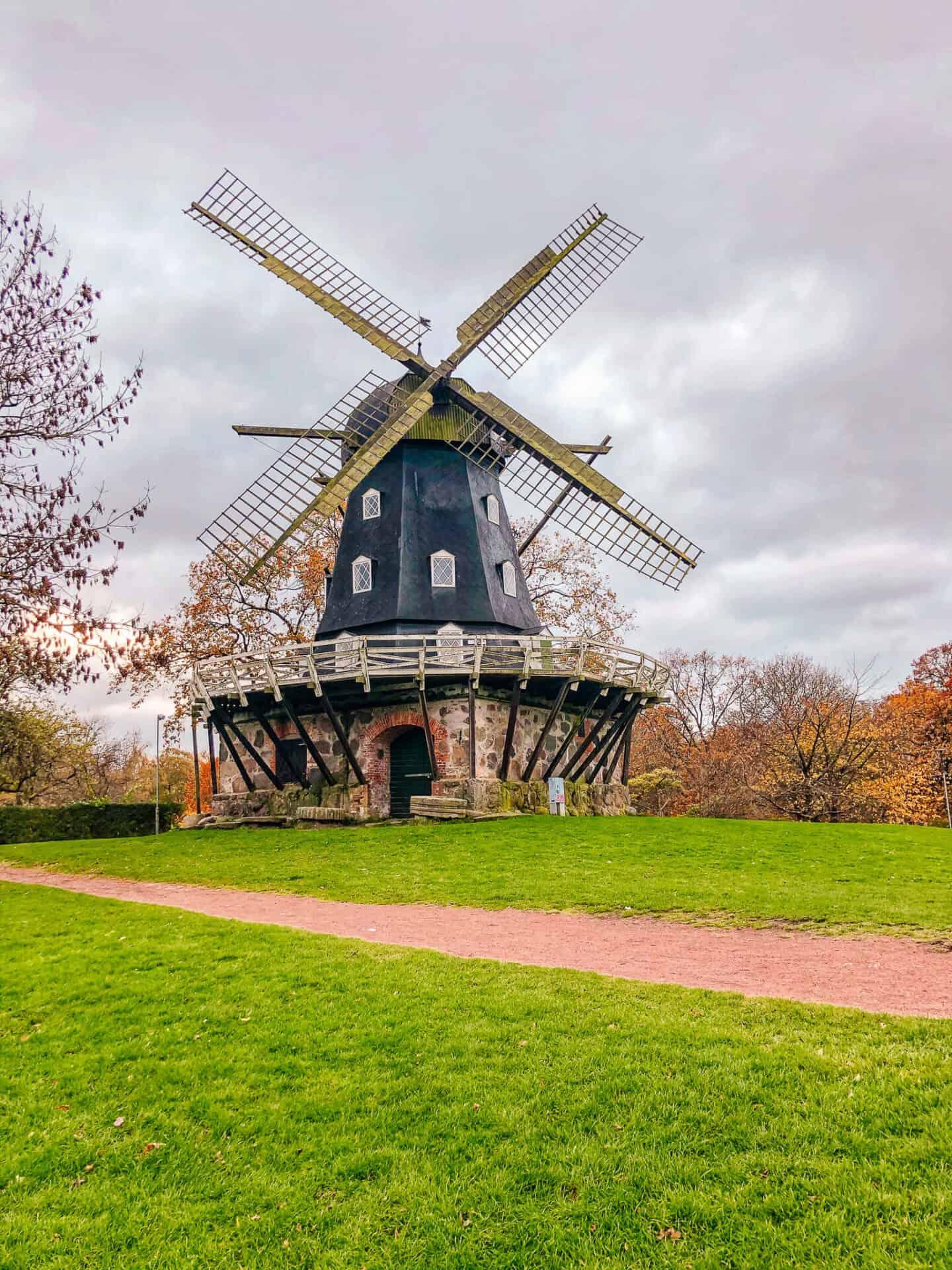 Blue windmill standing in green grass