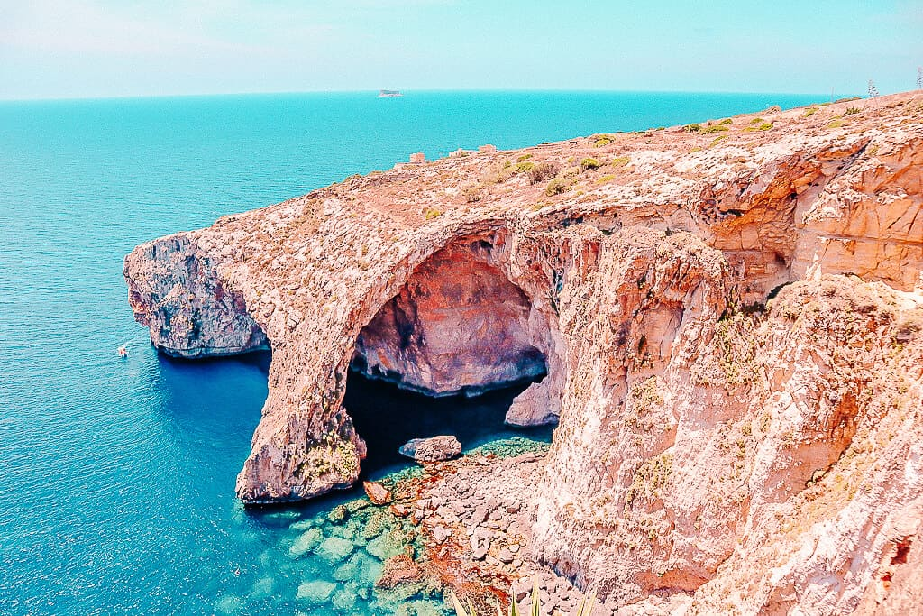 A natural stone structure with a cave in the middle surround by blue ocean waters.
