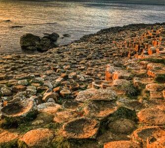 Basalt hexagonal columns on the coast at sunset