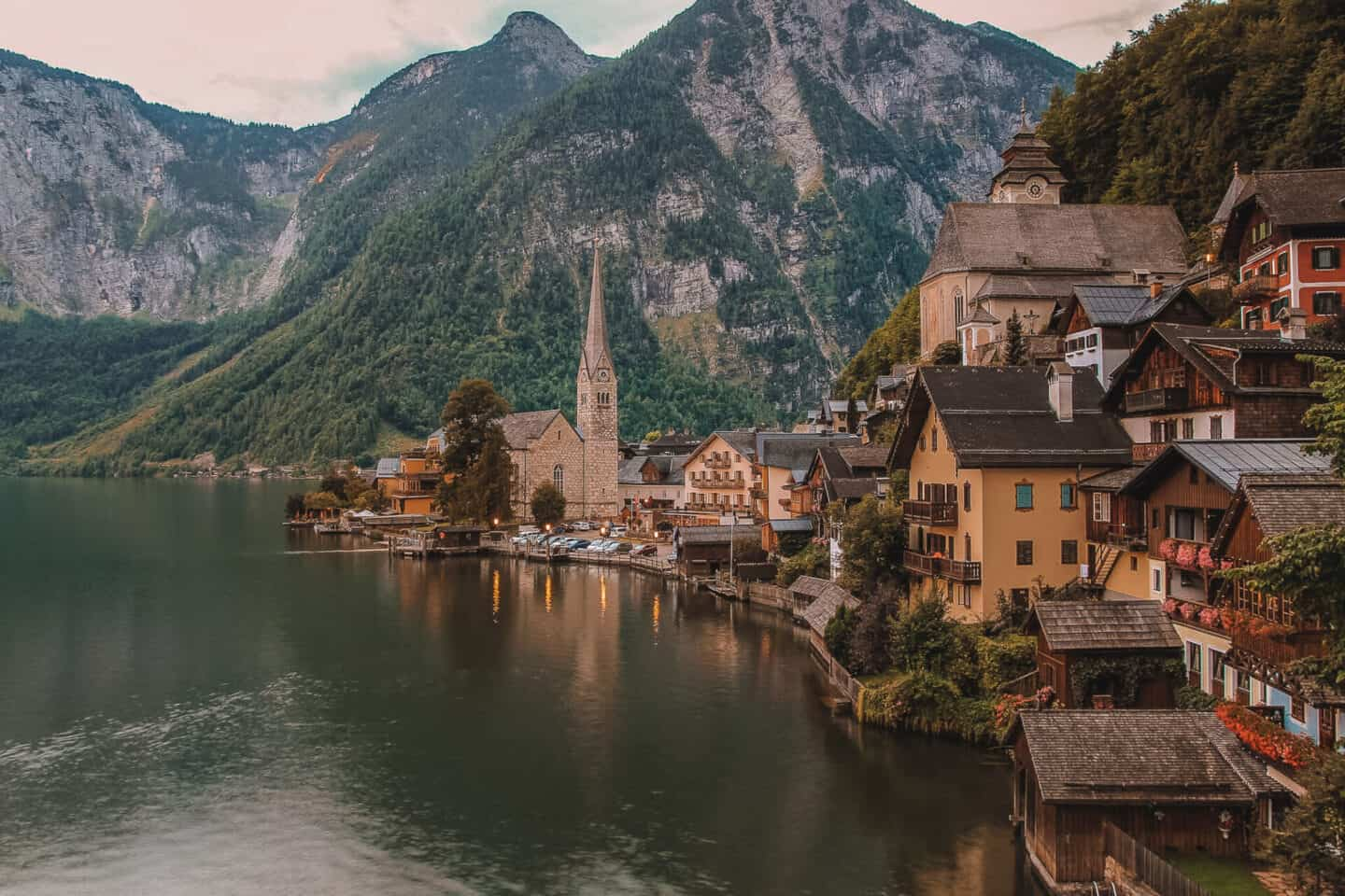 An Austrian village in between green mountains over looking a large lake.