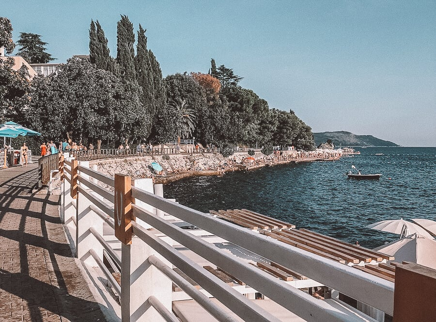 A white picket fence lining the ocean with green trees in the background -Herceg Novi, Montenegro