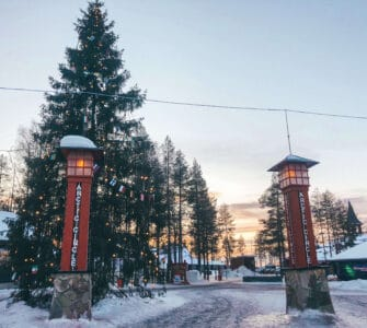 Two red poles with lamps on top in front of a snowy Christmas tree with the sun setting in the back ground