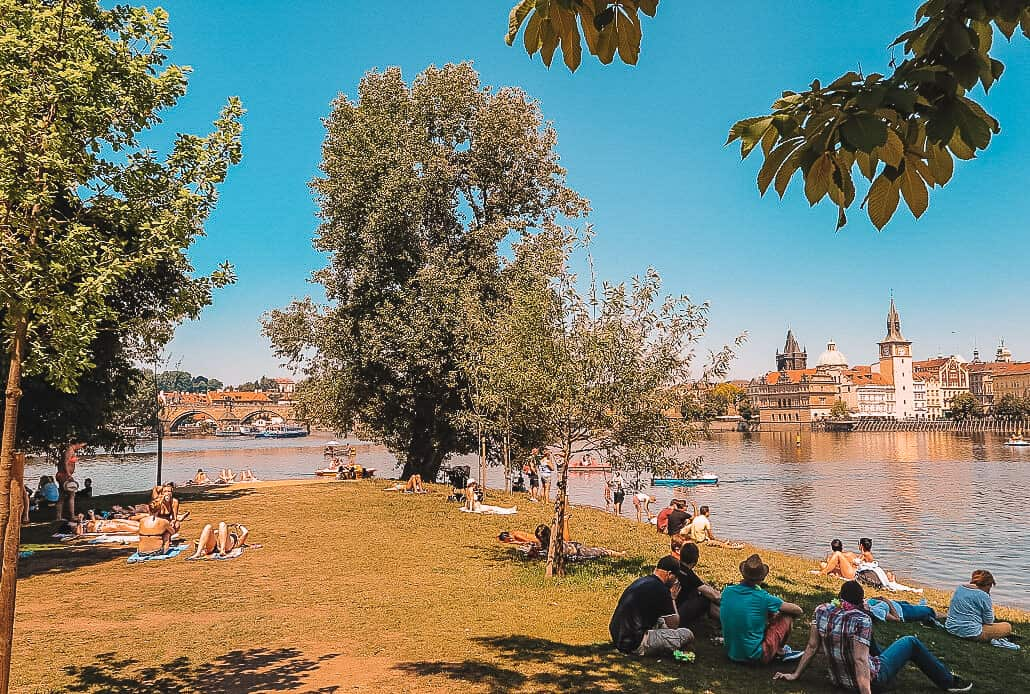 People relaxing on the grass of a river bank over looking an old European city under the shade of trees.