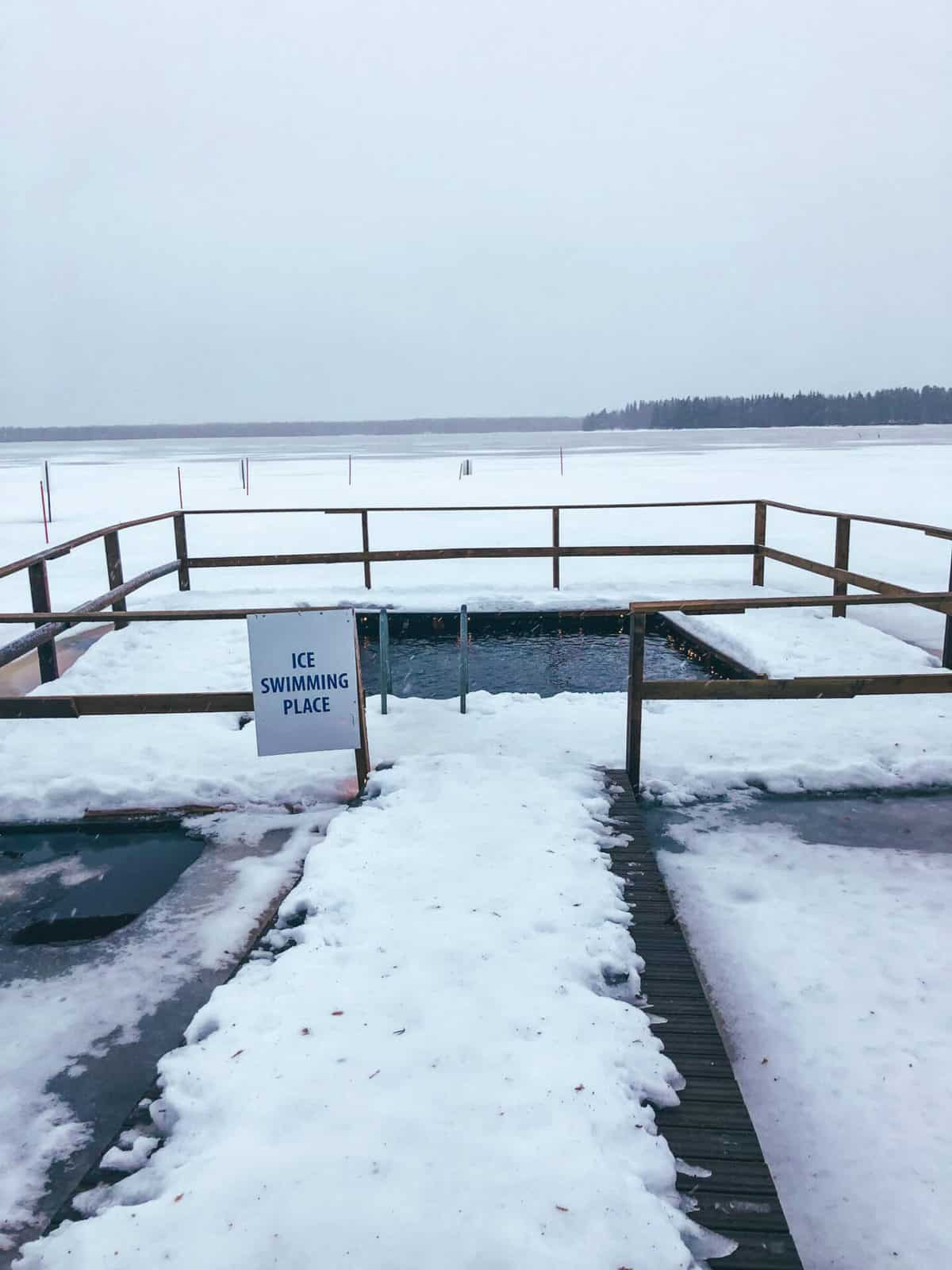 An ice pool on the side of a frozen lake surrounded by snow