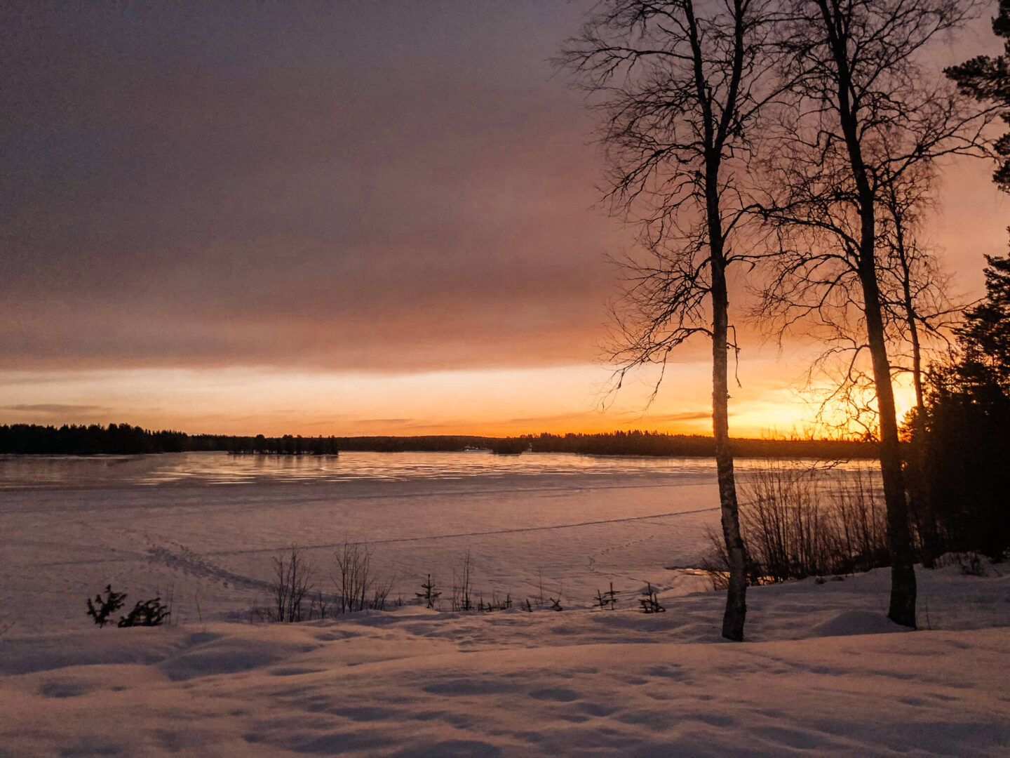 Sun setting over a frozen lake surrounded by snow
