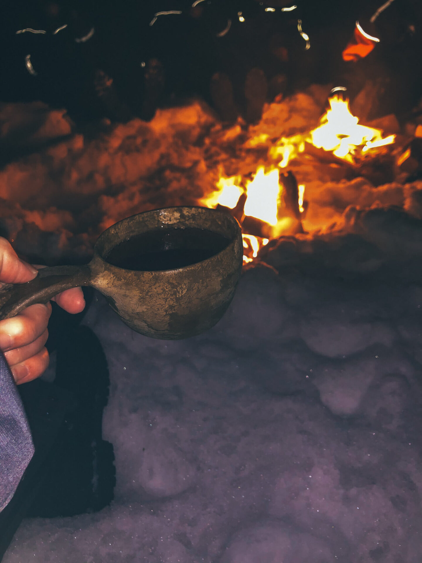 A traditional finnish cup in front of a fire on the snow