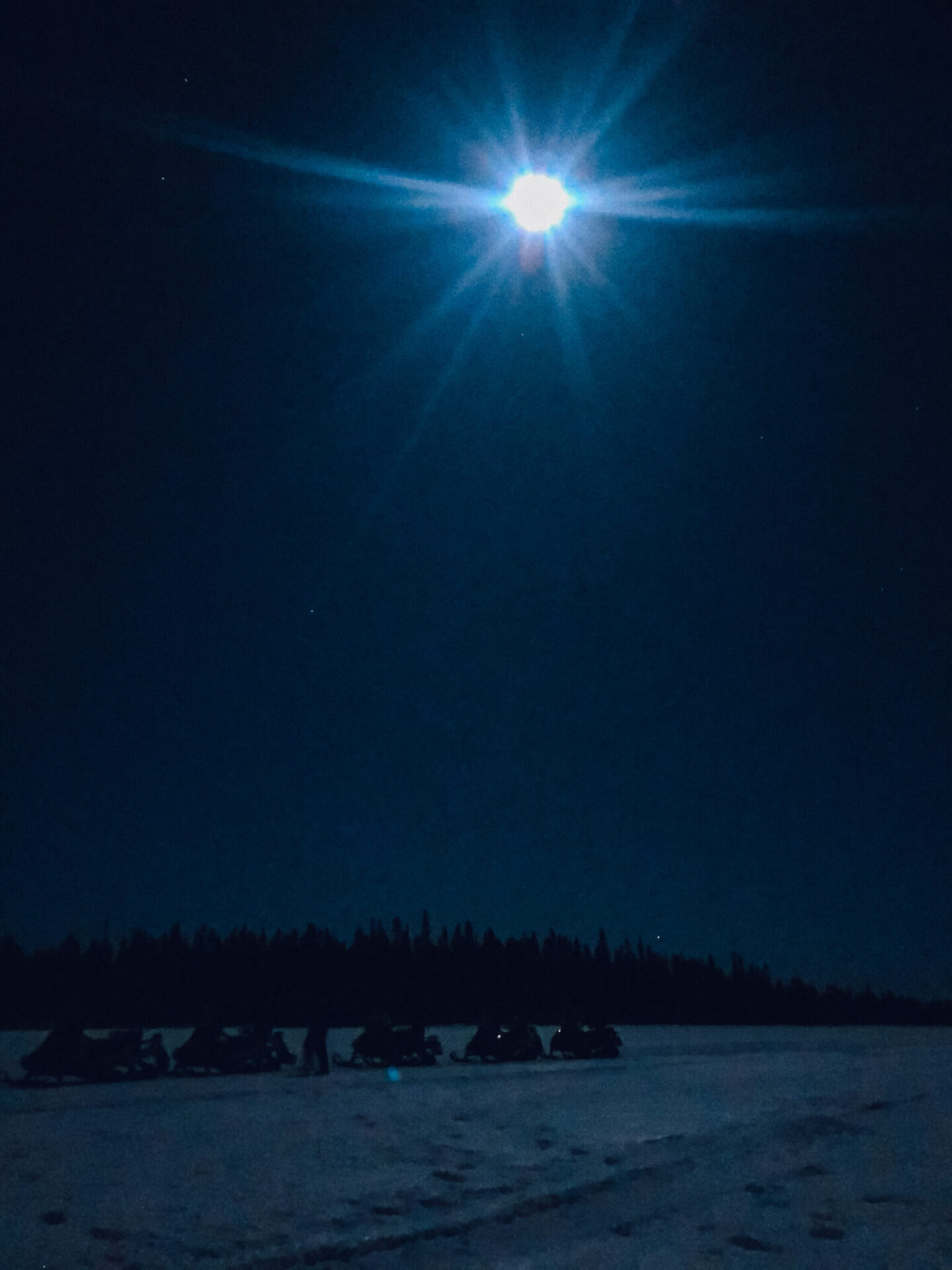 The moon over snowmobiles sitting on snow