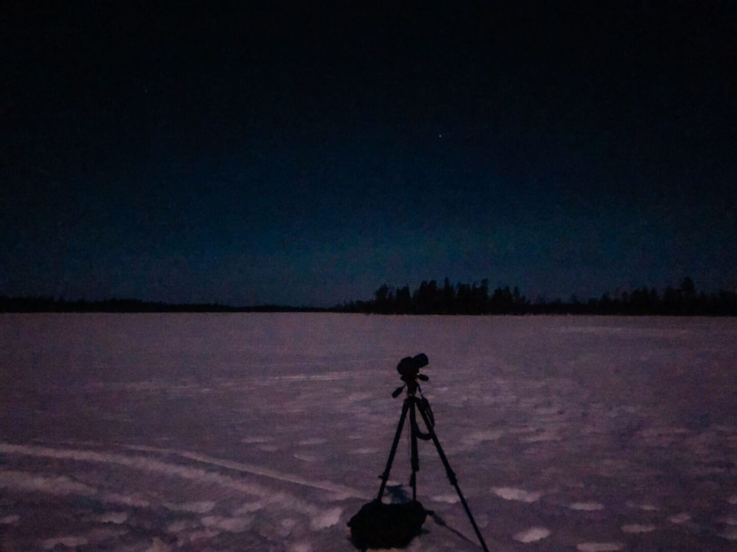 A camera sitting on a tripod in the snow with the northern lights faintly in the sky