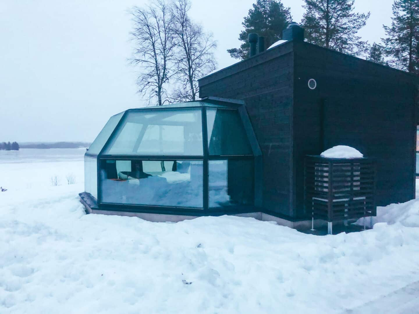 A glass igloo surrounded by snow