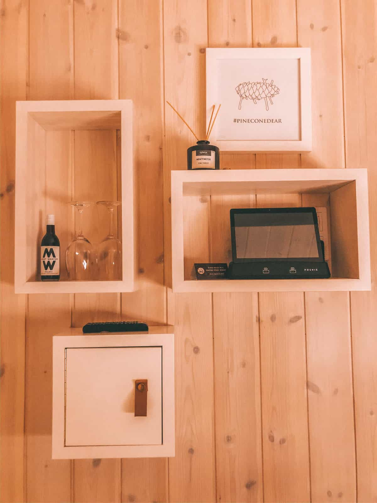 Floating boxes on a wall with a tablet, wine and wine glasses and a painting
