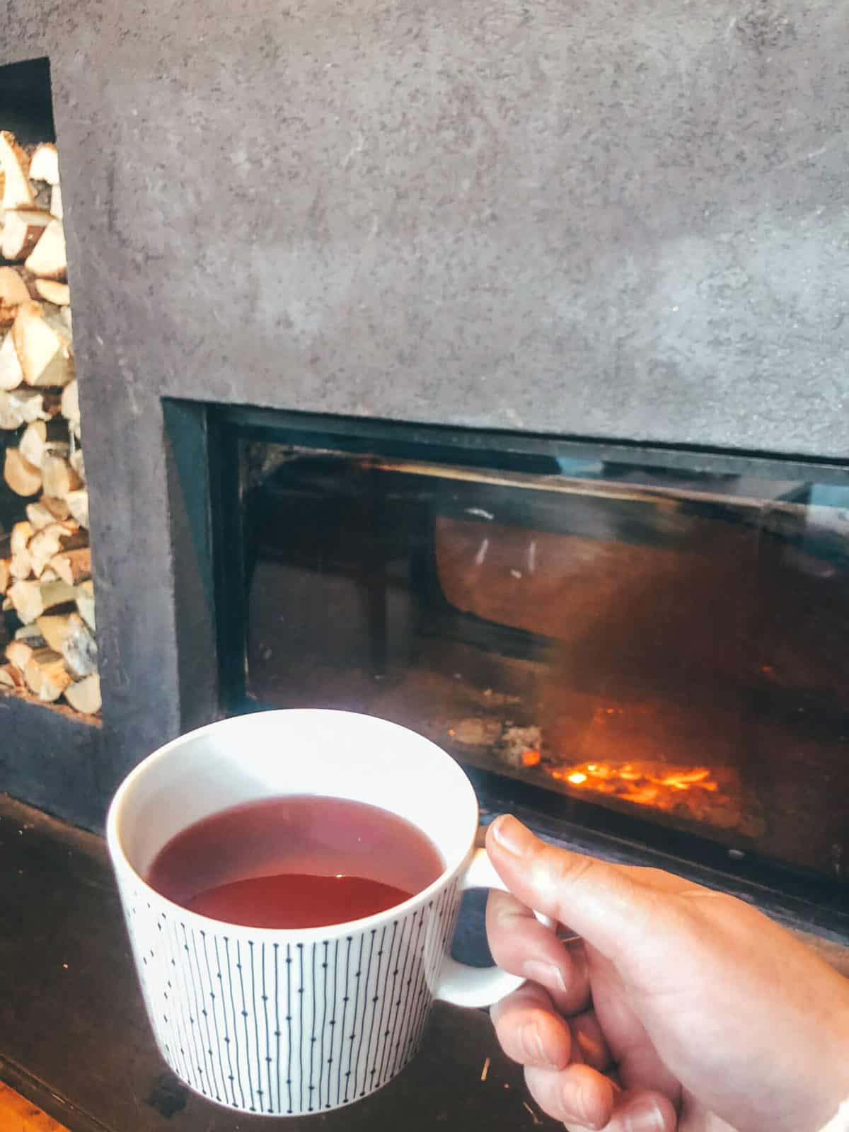 A hand holding a white mug with a red drink in the mug in front of a fire