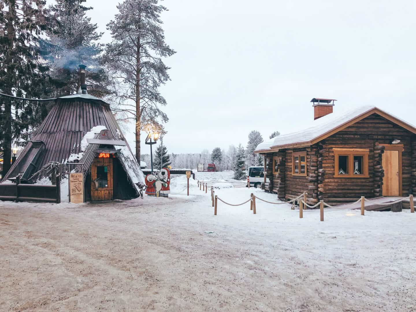 A Finnish Teepee next to a log cabin surrounded by snow