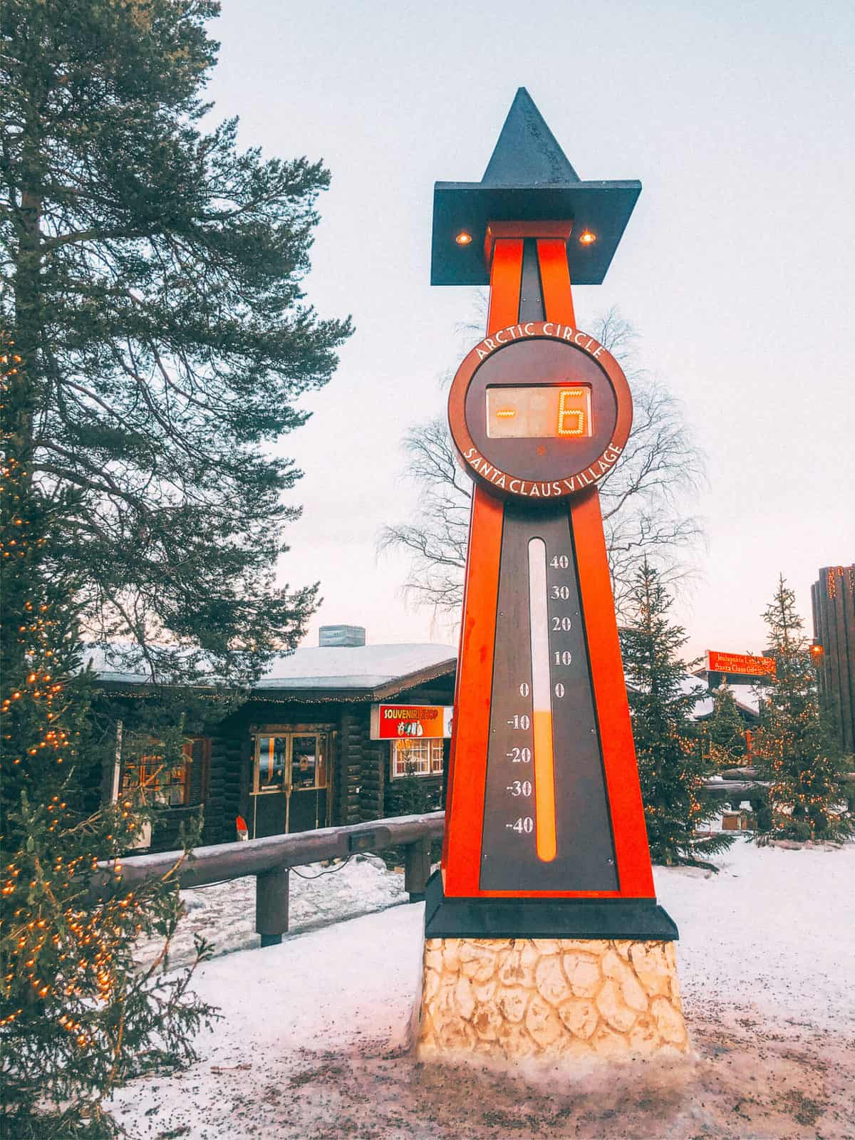 A red post surrounded by snowing showing a thermometer reading -6 degrees