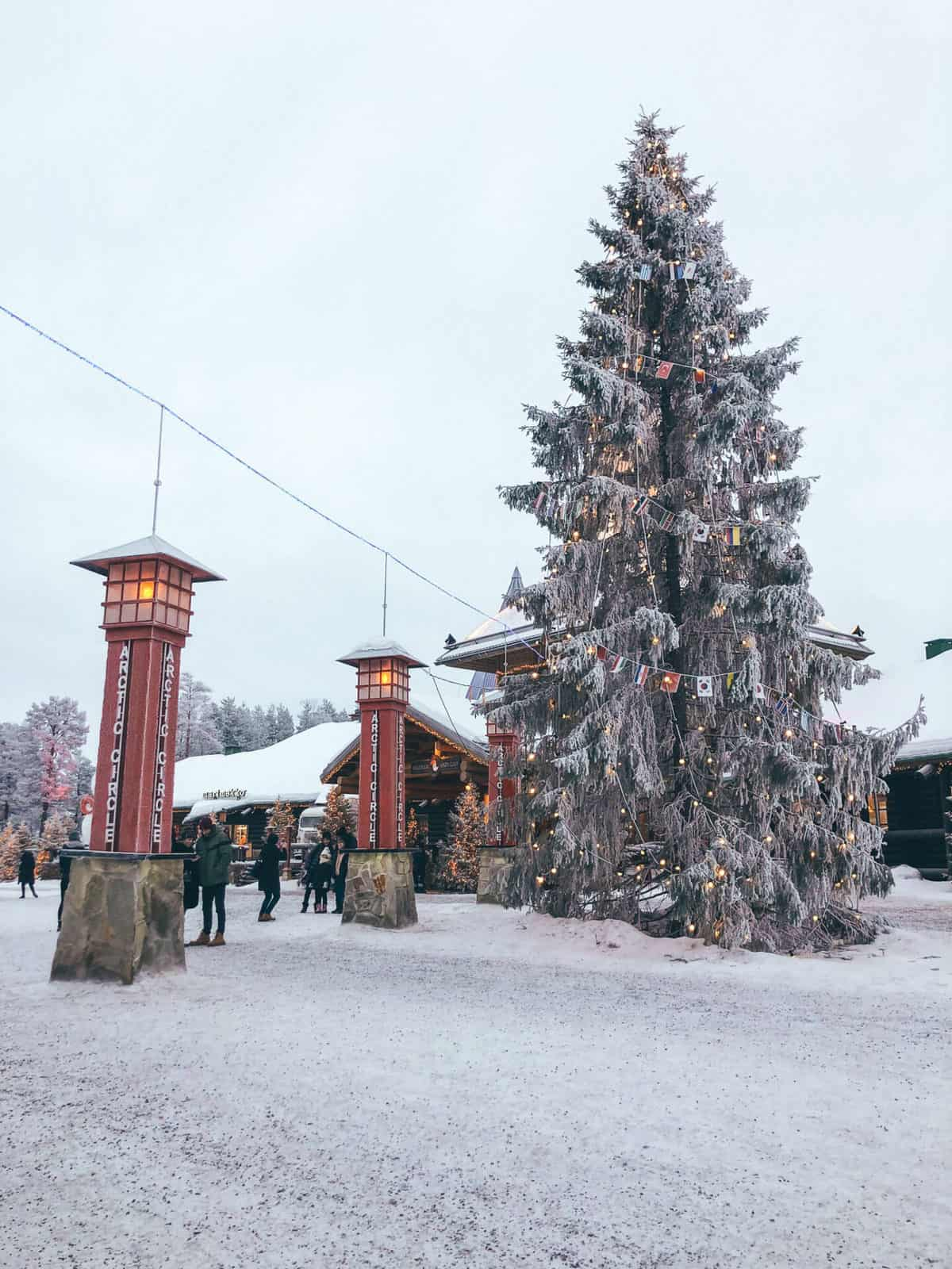 """Two red light poles reading """"Arctic Circle"""" next a huge snow covered tree"""