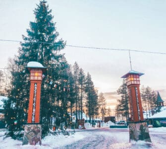 Two lamp posts with Arctic Circle written on them in front of a large Christmas tree in the snow