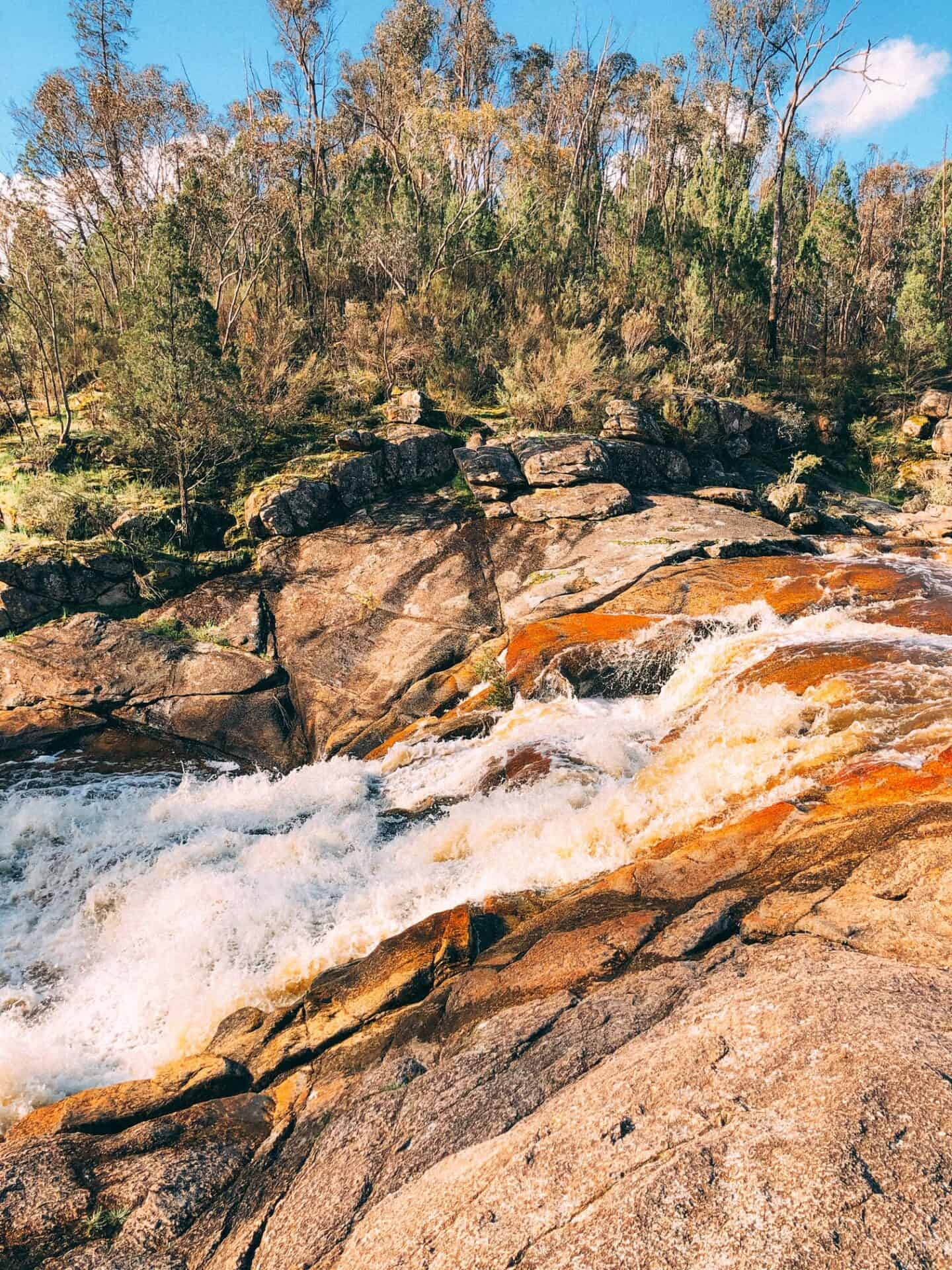 A water fall flowing over rocks with an birgh orange colour. Trees line the banks of the waterfalls