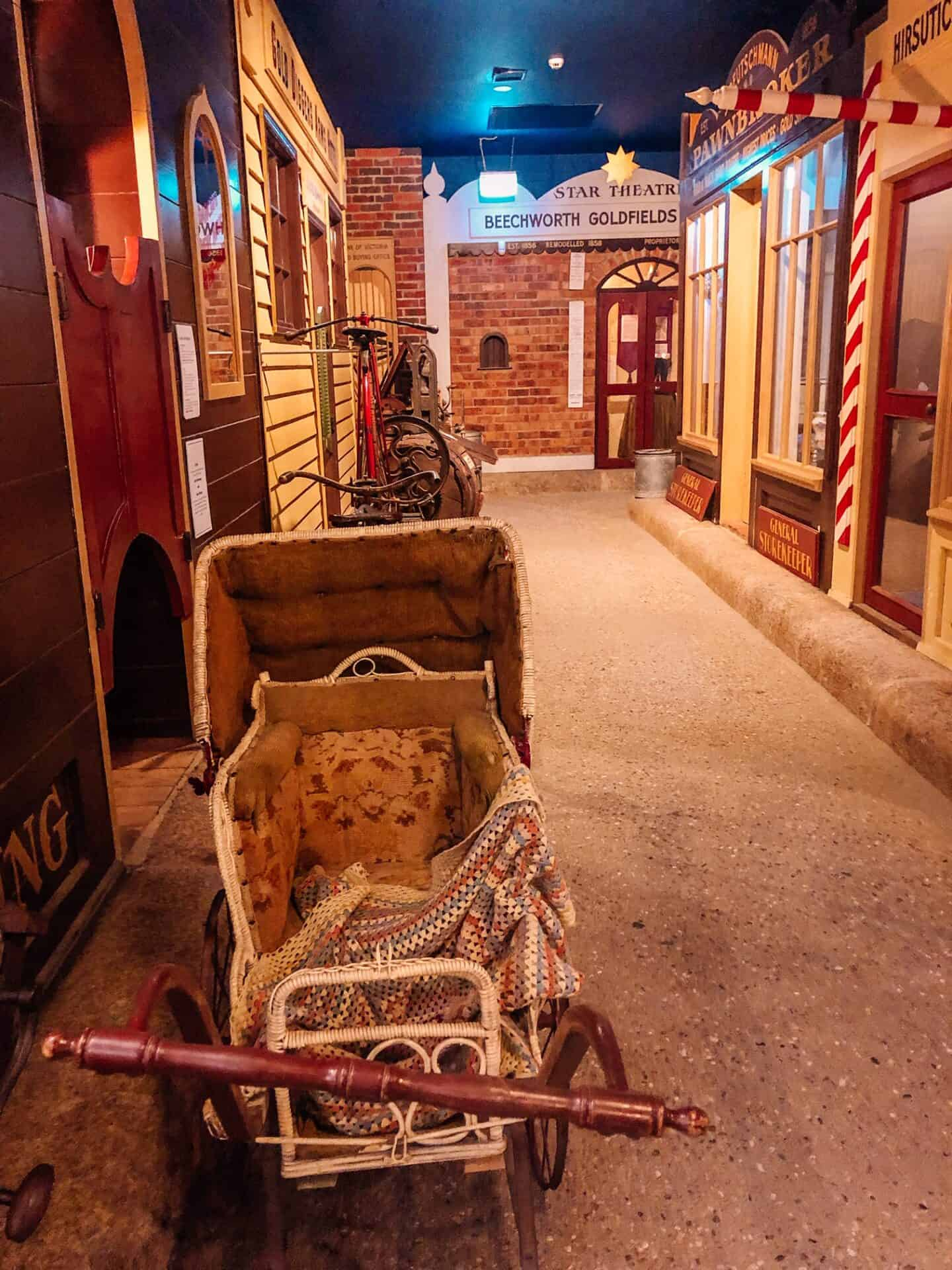 A mock up of a Victorian street. The street is lined with shops and an old pram is parked on the street.