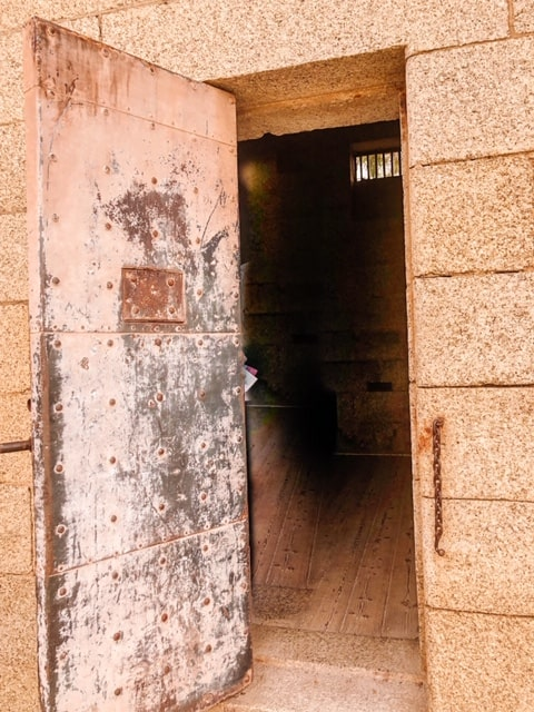 Old Heavy door on a sandstone building leading into a dark gaol cell.