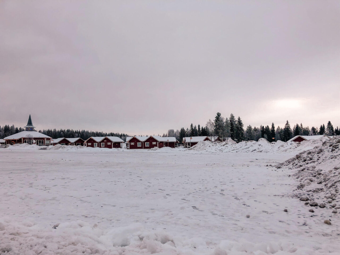 A snow field with red houses in the background