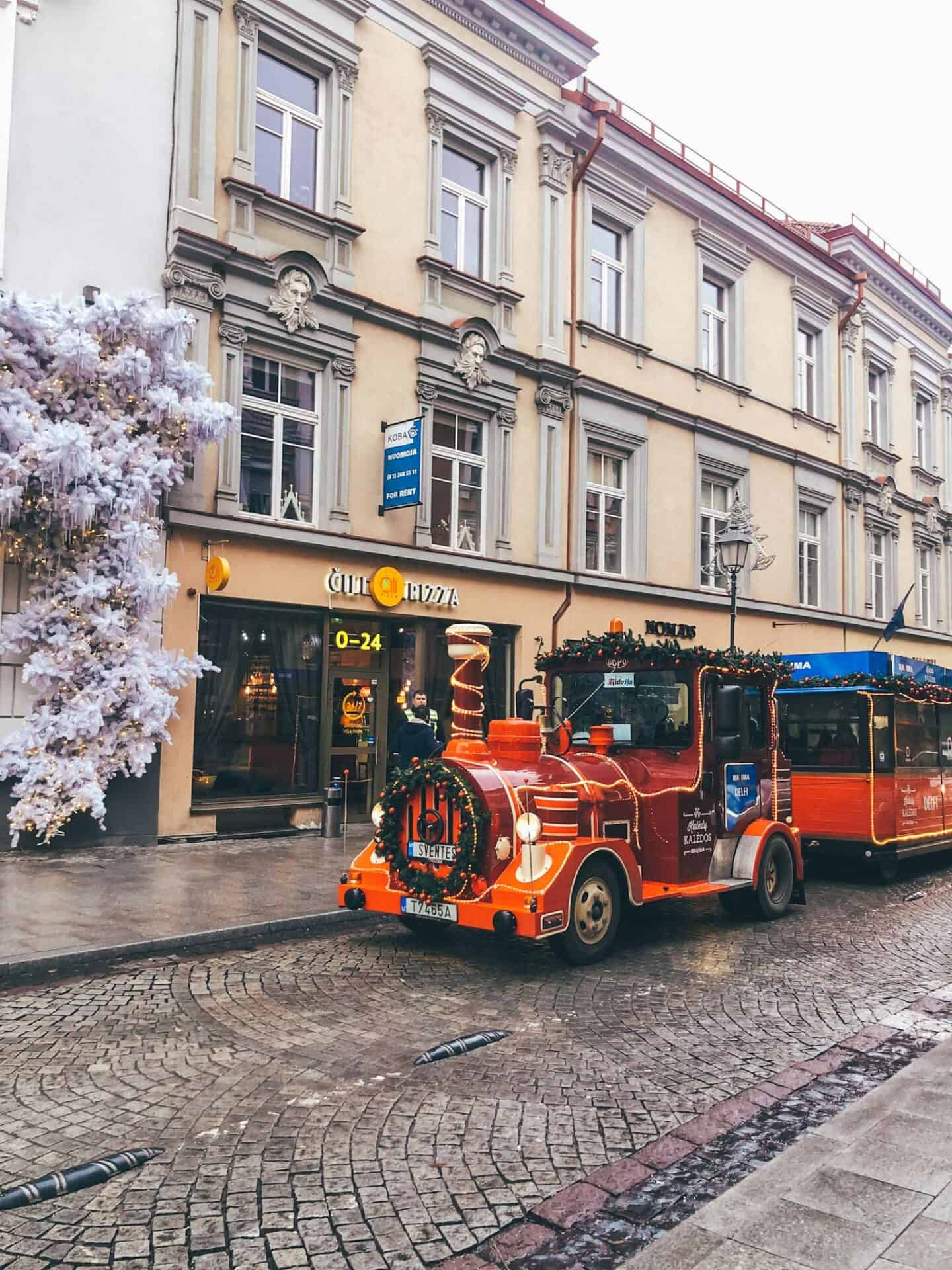 A red train park in front of old buildings.