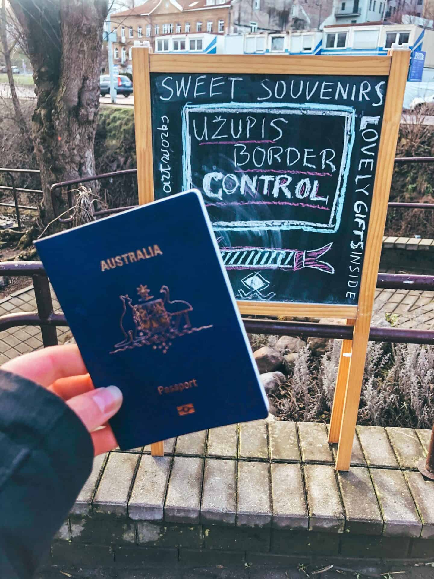 An Australian passport in front of a board saying Uzupis border control