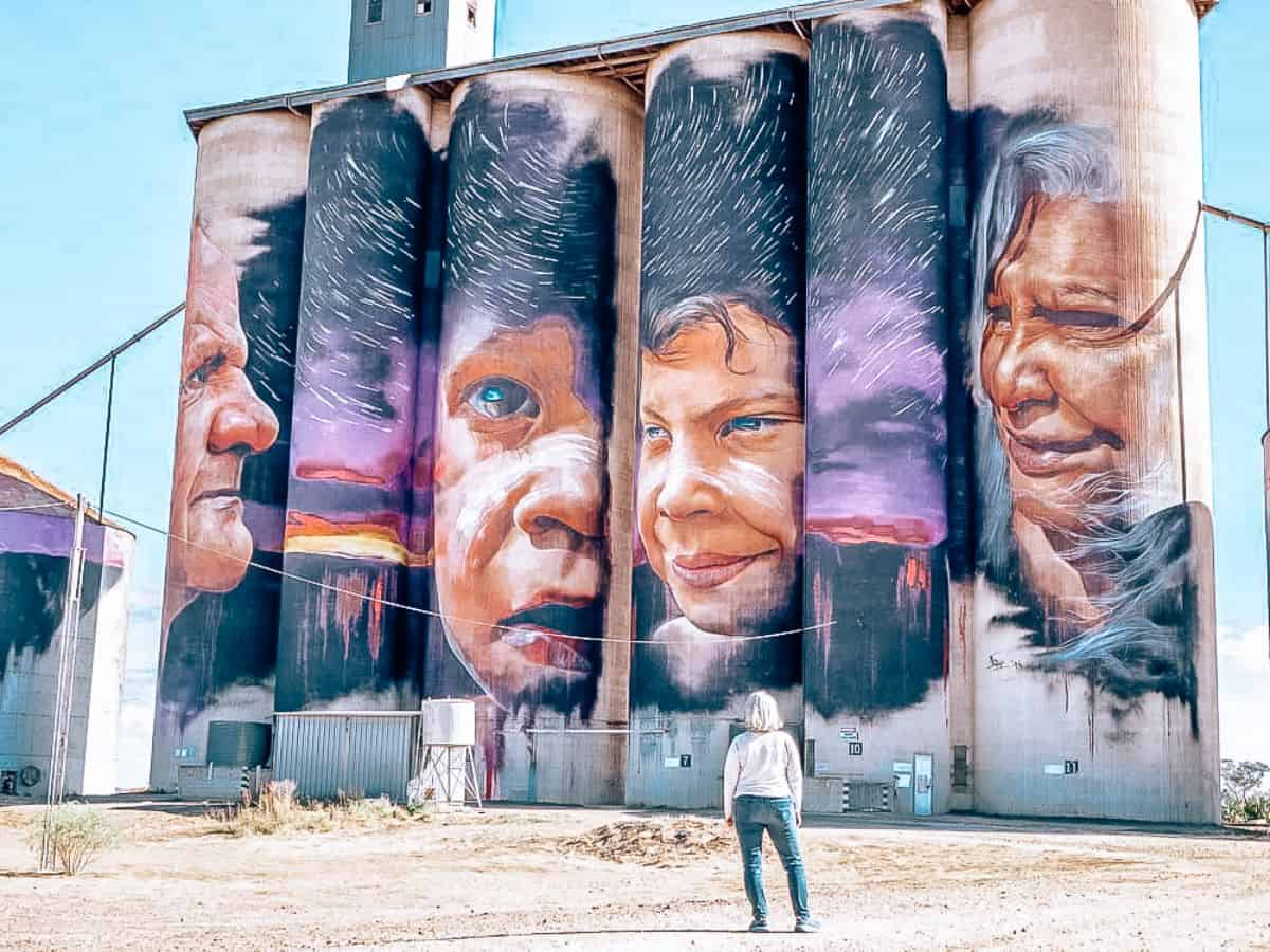 A person standing in front of silos covered in paintings