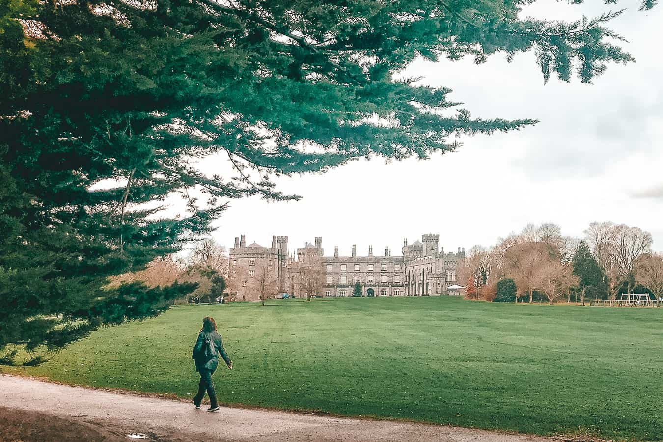 A person walking passed a castle in the distance