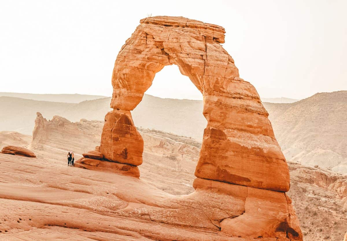 Two people standing next to a big rock arch