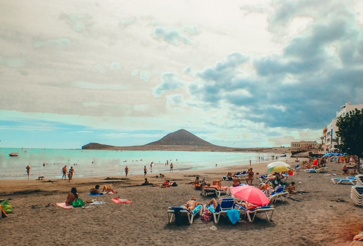 Bright umbrellas on a beach with a mountain overlooking the ocean