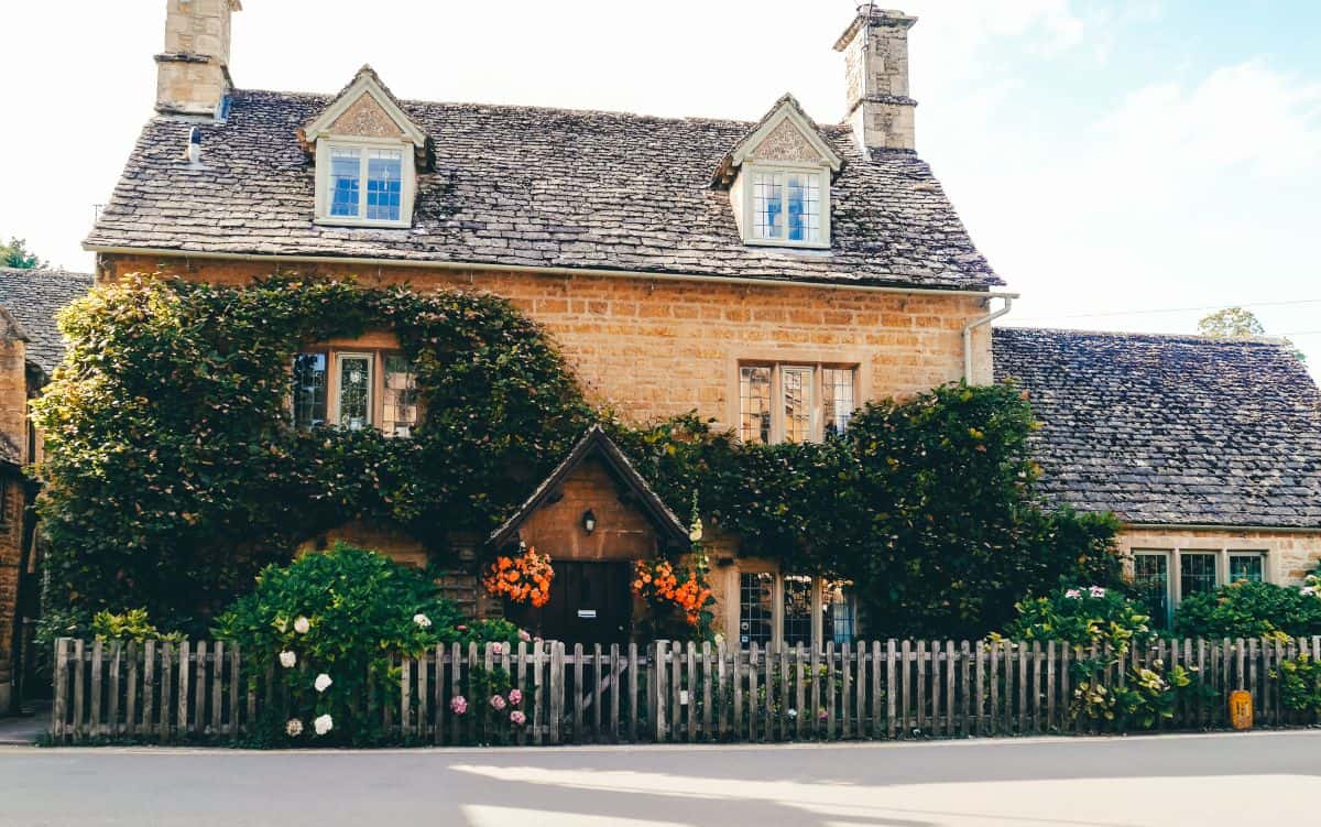 An English cottage covered in flowers and greenery