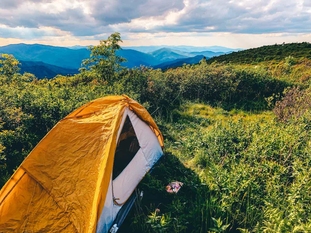 A yellow tent in the grass overlooking mountains