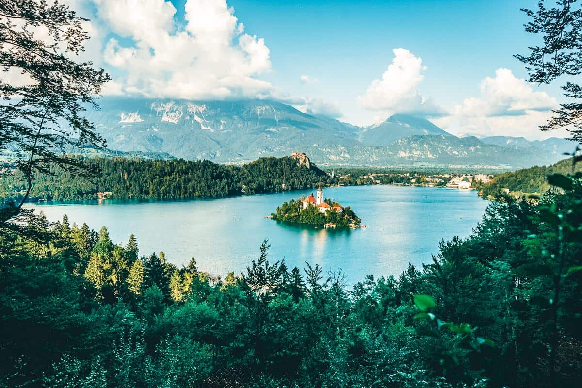 A view over a church on an island in the middle of lake surrounded by mountains