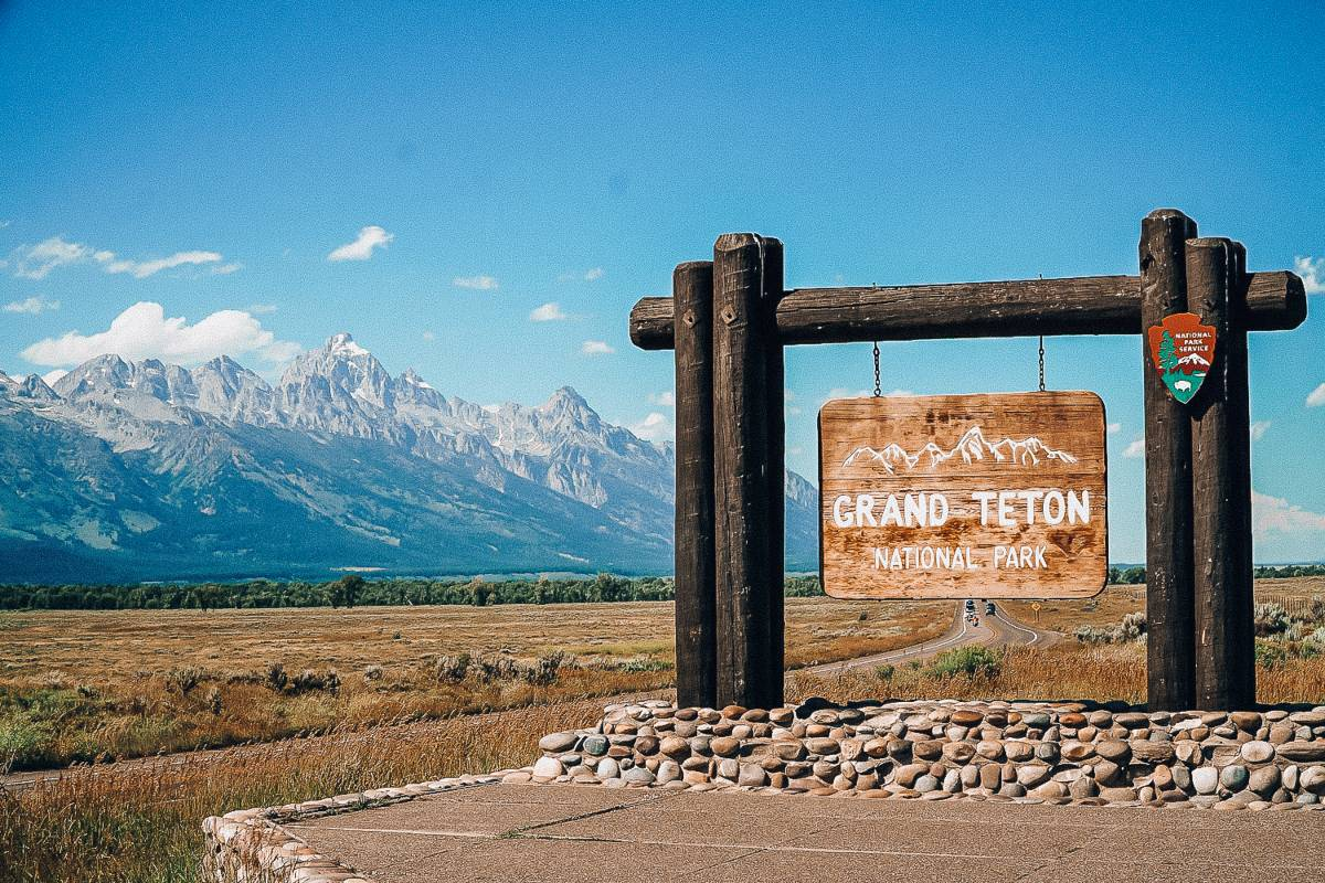 Grand teton national park sign in front of snow capped mountains