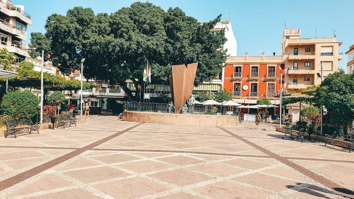 Town square with an orange building at the end and trees
