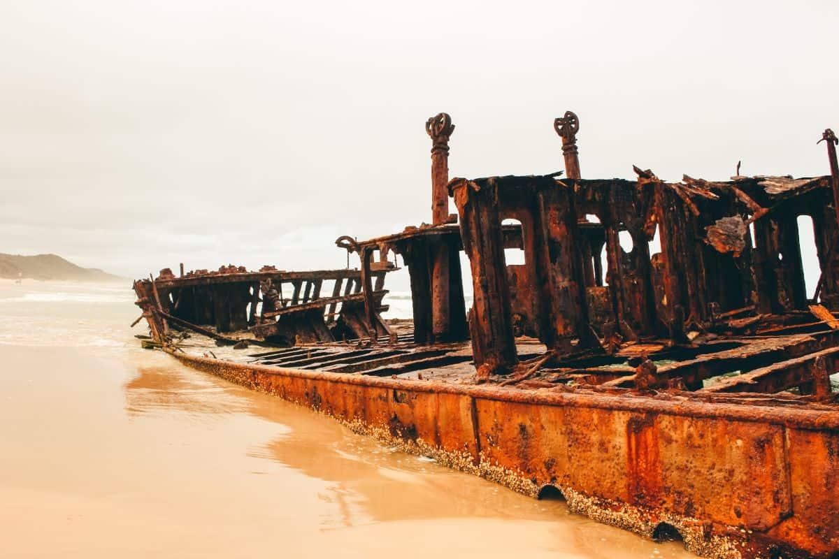 A rusty shipwreck on a beach