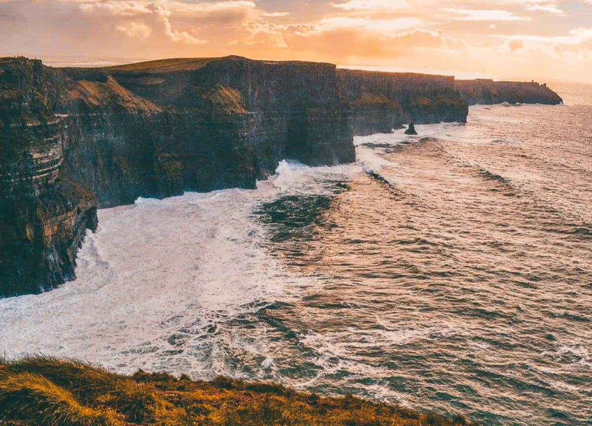 Large cliffs rising out of the ocean with the sunsetting in the background