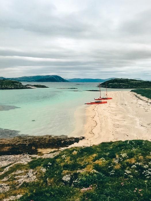 Kayaks sitting on the sand on edge of a blue ocean